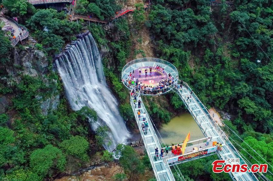 An aerial view of a glass viewing platform along a cliff at the Gulongxia scenic spot in Qingyuan City, South China\'s Guangdong province, June 28, 2018. The structure also features a massive circular glass observation deck suspended at the end of the bridge, jutting out 72 meters from the cliff edge. (Photo: China News Service/Xu Qingqing)