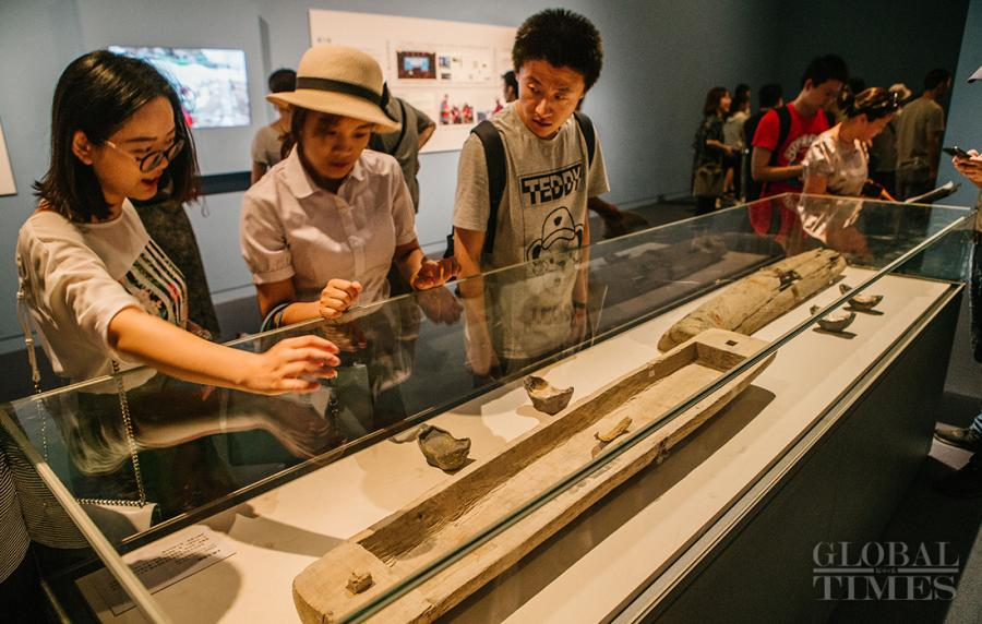 Visitors view a wooden sheath discovered in the ruins that verifies a legend saying that Zhang Xianzhong used to hide silver bars inside wooden sheaths.  (Photo: Li Hao/GT)