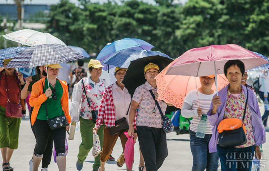 A tour group holds parasols during a visit near Beijing\'s Tiananmen Square on Thursday.  (Photo: Li Hao/GT)