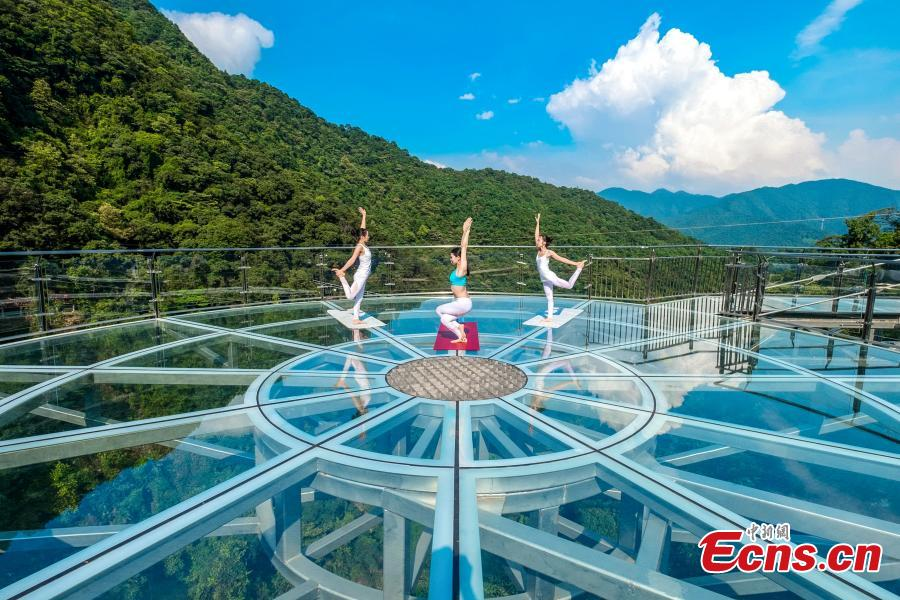 Yoga lovers perform at the opening ceremony of a glass walkway in Qingyuan City, South China's Guangdong Province, June 28, 2018. The structure also features a massive circular glass observation deck suspended at the end of the bridge, jutting out 72 meters from the cliff edge. (Photo: China News Service/Zeng Linghua)