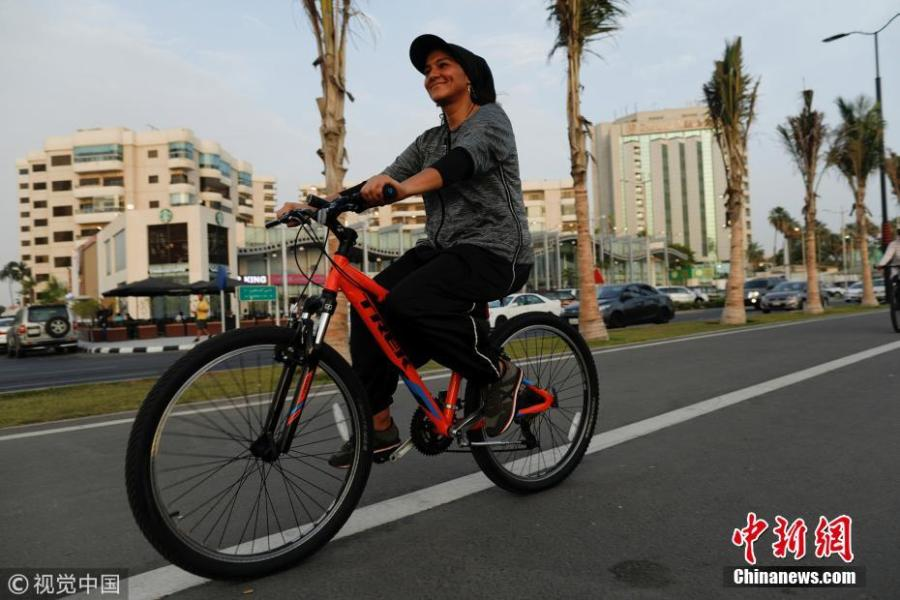 """Eman Joharjy, a fashion designer in one of her own creations, cycles along Jaddah\'s Corniche, Saudi Arabia, June 24, 2018. In 2007, frustrated by a lack of abayas made for running or cycling, Joharjy designed one for herself. She began making them for friends and selling what she dubbed the """"sporty abaya"""". (Photo/Agencies)"""