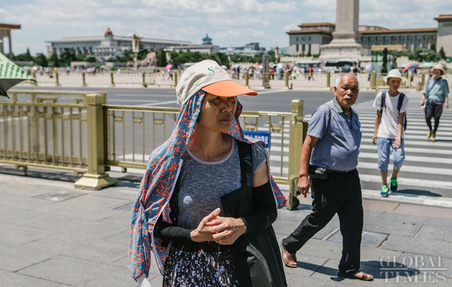A woman keeps covered to escape the sunshine in Beijing on Thursday as the city experiences a heat wave.  (Photo: Li Hao/GT)