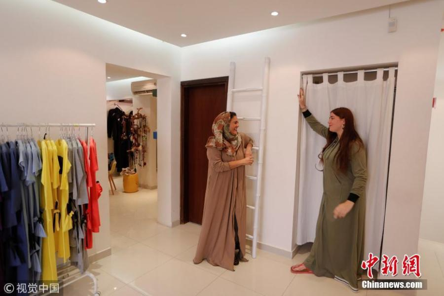 """Eman Joharjy (L), a fashion designer, smiles while standing with her employee as she tries on one of her creations at her shop in Jeddah, Saudi Arabia, June 23, 2018. In 2007, frustrated by a lack of abayas made for running or cycling, Joharjy designed one for herself. She began making them for friends and selling what she dubbed the """"sporty abaya"""". (Photo/Agencies)"""