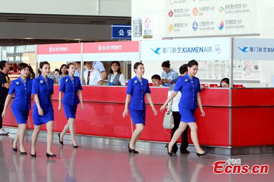 Staff members of the Tianjin Binhai International Airport show new uniforms at the airport, June 28, 2018. (Photo/China News Service)