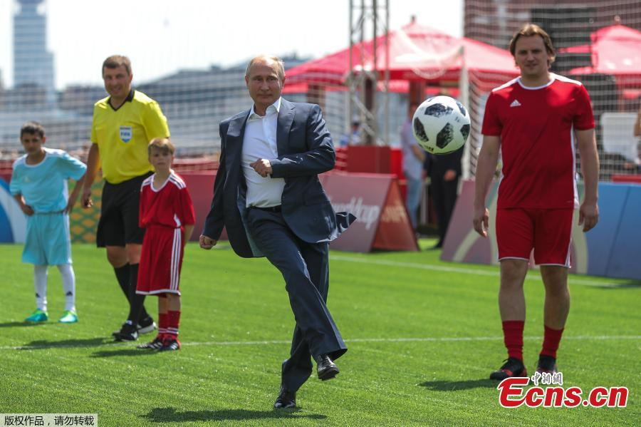 Russian President Vladimir Putin kicks the ball during the opening of an exhibition match in the World Cup Football Park in Red Square in central Moscow, Russia June 28, 2018. Young Russian footballers taking part in the exhibition match had the chance to show-off their skills in front of FIFA Legends as well as Gianni Infantino and Vladimir Putin. (Photo/Agencies)