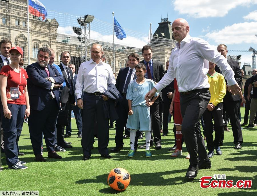 FIFA President Gianni Infantino (Right), kicks the ball as Russian President Vladimir Putin, center, looks at him during an opening friendly soccer match between two children teams and FIFA legends at a Football Park in Red Square during the 2018 soccer World Cup in the Spartak Stadium in Moscow, Russia, Thursday, June 28, 2018. (Photo/Agencies)