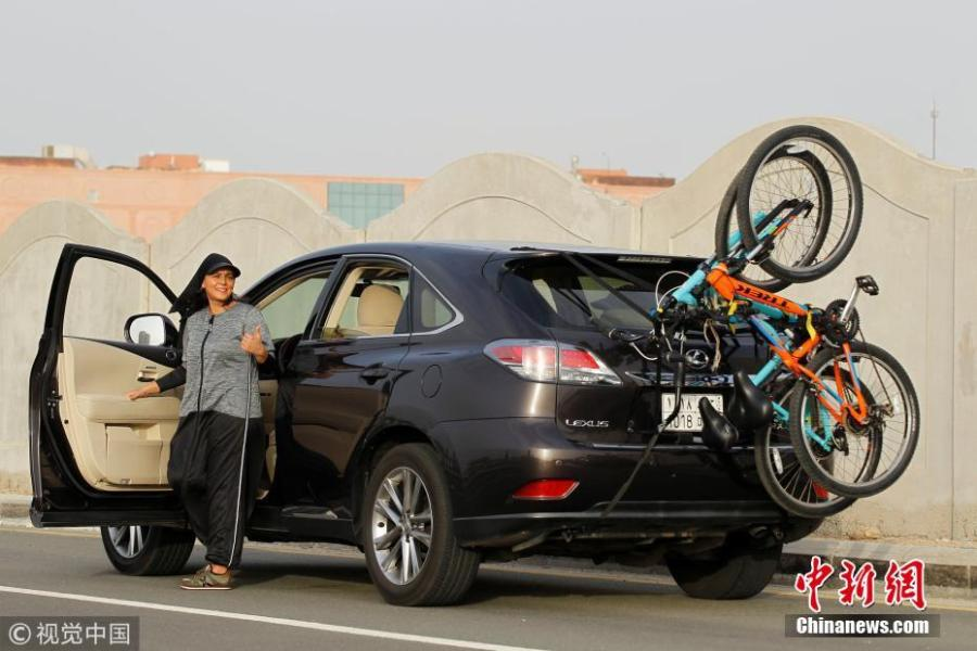 Eman Joharjy, a fashion designer in one of her own creations, reacts as she is about to drive to Jeddah\'s Corniche to cycle, Saudi Arabia, June 24, 2018. In 2007, frustrated by a lack of abayas made for running or cycling, Joharjy designed one for herself. She began making them for friends and selling what she dubbed the \