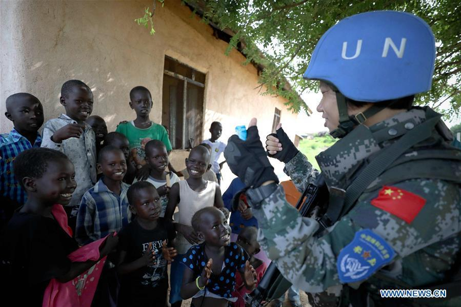 Chinese peacekeeper Yu Peijie (R) sings songs with local children in Juba, South Sudan, on April 30, 2018. Yu Peijie, 26-year-old, is the leader of the female peacekeeper unit of Chinese peacekeeping infantry batallion to South Sudan. She has a nickname called \