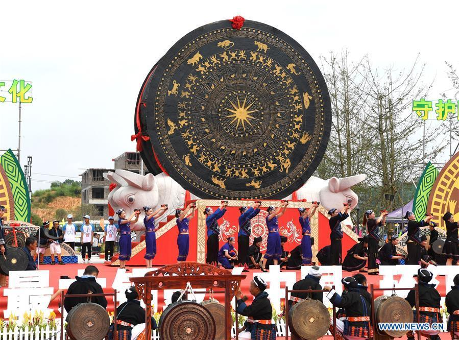 People celebrate beside a gigantic bronze drum in Huanjiang Maonan Autonomous County, south China\'s Guangxi Zhuang Autonomous Region, June 29, 2018. The drum measures 6.68 meters in diameter and weighs 50 tons. It was recognized as the largest bronze drum by Guinness World Records. (Xinhua/Zhou Hua)