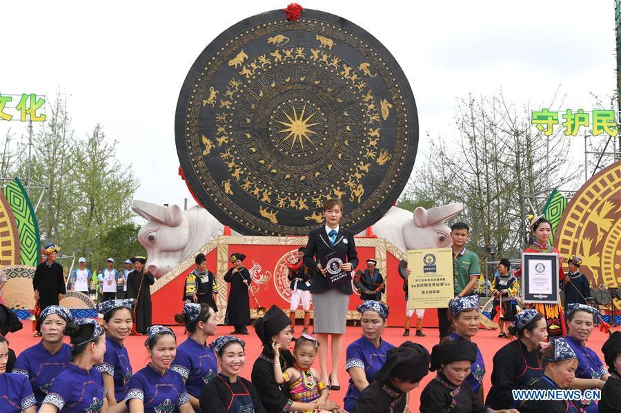Photo taken on June 29, 2018 shows a ceremony to present the certificate for the world\'s largest bronze drum by Guinness World Records as the gigantic bronze drum (rear, C) is seen in Huanjiang Maonan Autonomous County, south China\'s Guangxi Zhuang Autonomous Region. The drum measures 6.68 meters in diameter and weighs 50 tons. It was recognized as the largest bronze drum by Guinness World Records. (Xinhua/Zhou Hua)
