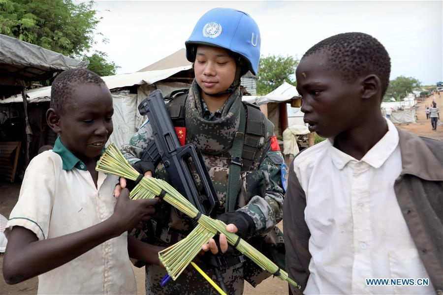 Local children present a tool rifle to Chinese peacekeeper Yu Peijie (C) as a gift at No.1 refugee camp of the United Nations, South Sudan, on April 30, 2018. Yu Peijie, 26-year-old, is the leader of the female peacekeeper unit of Chinese peacekeeping infantry batallion to South Sudan. She has a nickname called \