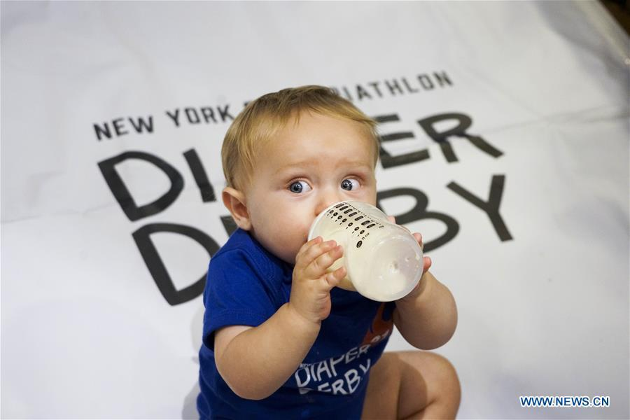 A baby drinks milk during the Diaper Derby 2018 in New York, the United States, June 29, 2018. Diaper Derby 2018, a baby crawling contest, was held here on Friday. Around 30 babies competed to crawl across a 12-foot (3.66 meters) long mat. (Xinhua/Lin Bilin)
