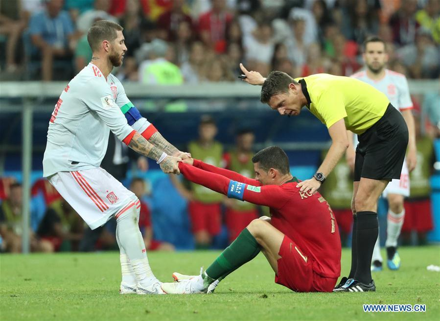 Sergio Ramos (L) of Spain tries to help Cristiano Ronaldo of Portugal during a group B match between Portugal and Spain at the 2018 FIFA World Cup in Sochi, Russia, June 15, 2018. The match ended in a 3-3 draw. (Xinhua/Ye Pingfan)