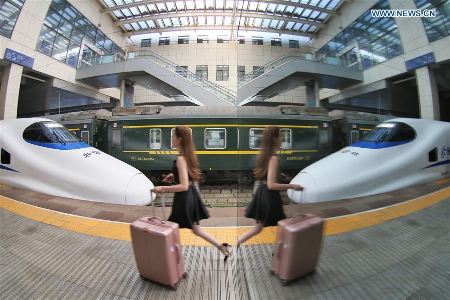 A passenger boards a bullet train at the Yantai Railway Station in Yantai, east China\'s Shandong Province, June 30, 2018. China\'s summer transport peak period will begin on July 1, with a total of 647 million passenger trips expected to be made by train. The period runs from July 1 to August 31, when students on summer vacation have time to travel or return home. (Xinhua/Tang Ke)