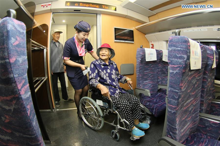 Conductor Zhang Xinxin (2nd R) helps a wheelchair user on the bullet train D6093 at the Yantai Railway Station in Yantai, east China\'s Shandong Province, June 30, 2018. China\'s summer transport peak period will begin on July 1, with a total of 647 million passenger trips expected to be made by train. The period runs from July 1 to August 31, when students on summer vacation have time to travel or return home. (Xinhua/Tang Ke)