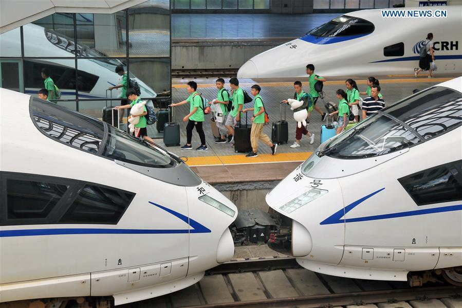 Children board a bullet train at the Yantai Railway Station in Yantai, east China\'s Shandong Province, June 30, 2018. China\'s summer transport peak period will begin on July 1, with a total of 647 million passenger trips expected to be made by train. The period runs from July 1 to August 31, when students on summer vacation have time to travel or return home. (Xinhua/Tang Ke)