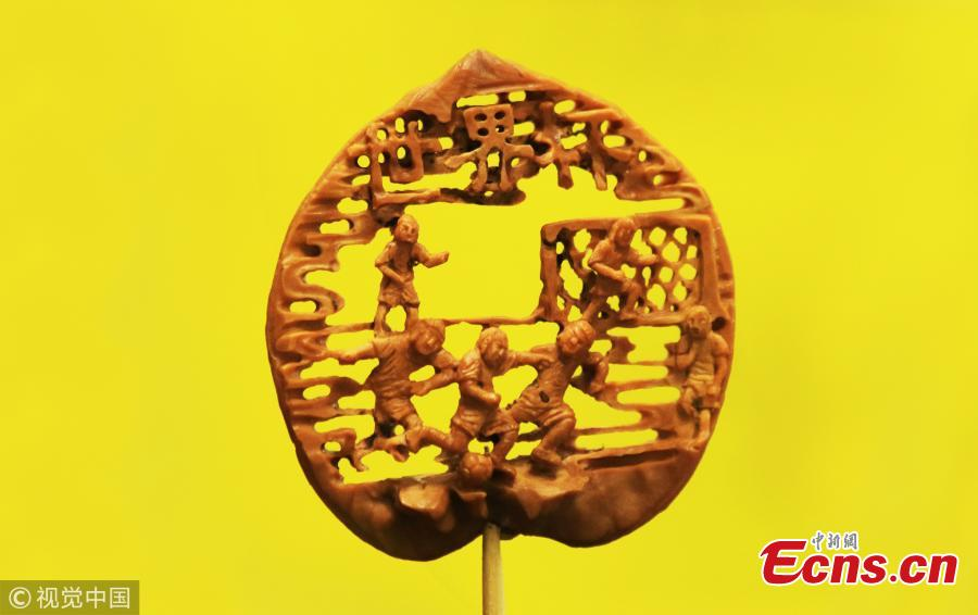 Folk artist Liu Jun, also a football fan, shows a peach pit creation in his home in Jining City, East China's Shandong Province, July 1, 2018. Liu's latest World Cup-inspired creation depicts six players competing on a coin-sized peach pit. Liu said he often stayed up late to watch the World Cup matches. (Photo/VCG)