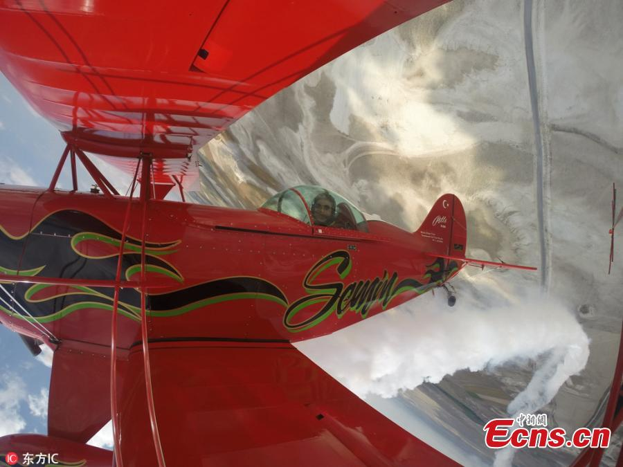 Semin Ozturk, Turkey\'s first professional female aerobatic pilot performs a demonstration flight with her \'Pitts S2-B\' plane that has Lycoming engine with 360 horsepower, at Necati Artan Facilities of Sivrihisar General Aviation Center in Eskisehir, Turkey, April 22, 2018. A 27-year-old aerobatic pilot, Semin experienced her first aerobatic flight performing when she was 12 years old with her father Ali Ismet Ozturk who is also an aerobatic pilot. On Sept. 19, 2015, she realized her first airshow at Sivrihisar General Aviation Center. Ozturk will attend the Aeromania Airshow which will take place between July 14-15 and host 35 aerobatic pilots from many countries. (Photo/IC)