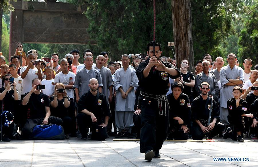 An American Kungfu enthusiast performs martial arts at Shaolin Temple on the Mount Songshan, central China\'s Henan Province, July 1, 2018. Over 200 Kungfu enthusiasts from America made a trip to the Shaolin Temple and performed martial arts with local monks. (Xinhua/Li An)