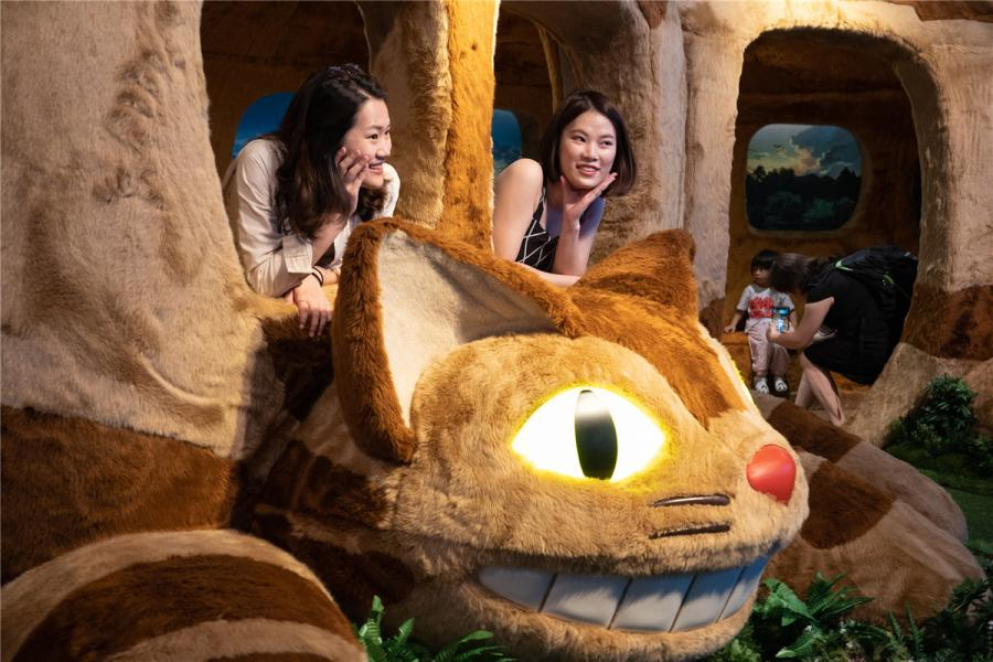 Visitors take a ride in the Tatsuo\'s bus featured in My Neighbor Totoro. (Photo/chinadaily.com.cn)