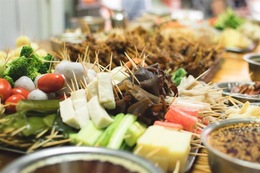 Lengzhanzhan is eaten by dipping the cooked ingredients on toothpicks in spicy sauce. (Photo/Shine.cn)
