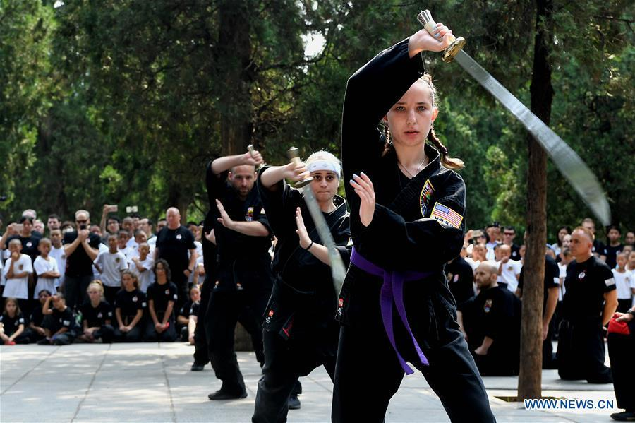 American Kungfu enthusiasts perform martial arts at Shaolin Temple on the Mount Songshan, central China\'s Henan Province, July 1, 2018. Over 200 Kungfu enthusiasts from America made a trip to the Shaolin Temple and performed martial arts with local monks. (Xinhua/Li An)