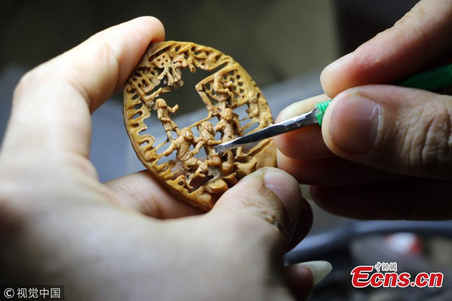 Folk artist Liu Jun, also a football fan, carves a peach pit in his home in Jining City, East China's Shandong Province, July 1, 2018. Liu's latest World Cup-inspired creation depicts six players competing on a coin-sized peach pit. Liu said he often stayed up late to watch the World Cup matches. (Photo/VCG)