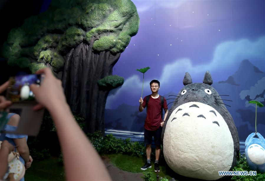 A man poses for a photo with Totoro, a cartoon figure in the Japanese animation fantasy film \