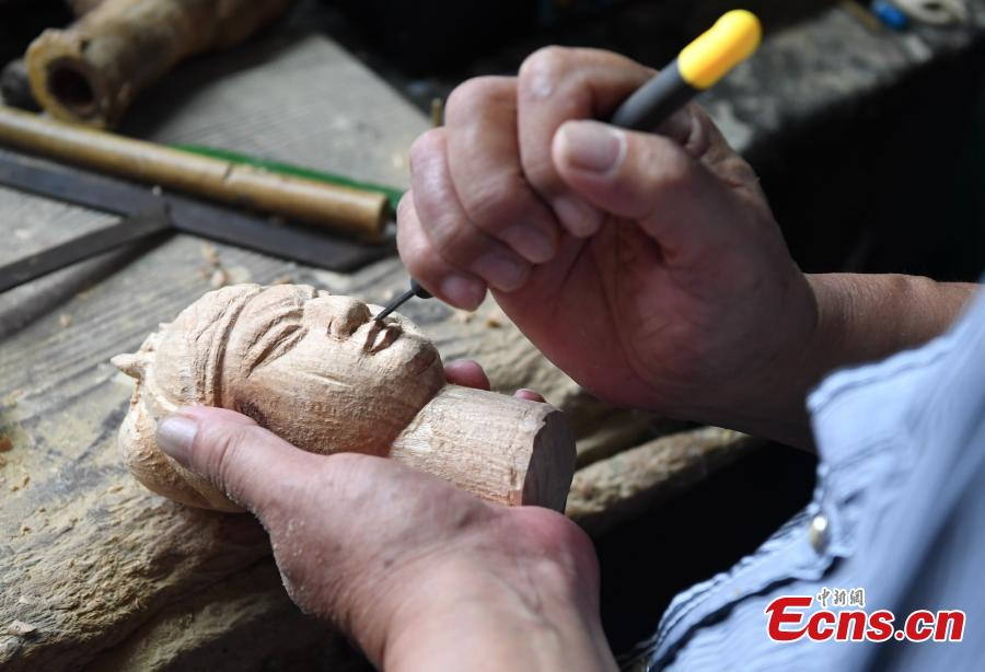 Folk artist Yang Yazhou makes a puppet head in his studio in Zhangzhou City, East China's Fujian Province, July 1, 2018. Zhangzhou has a history of puppetry going back more than two thousand years. Yang represents the fifth generation of his family to be involved with Fuchun-style glove puppets show, an intangible cultural heritage. He began learning to carve puppet heads when he was nine years old, taught by several masters. Yang said it takes tens of steps to finish carving a puppet-head in about three days. Yang's sister specializes in dressing the puppets, his brother in puppet performance. (Photo: China News Service/Zhang Bin)