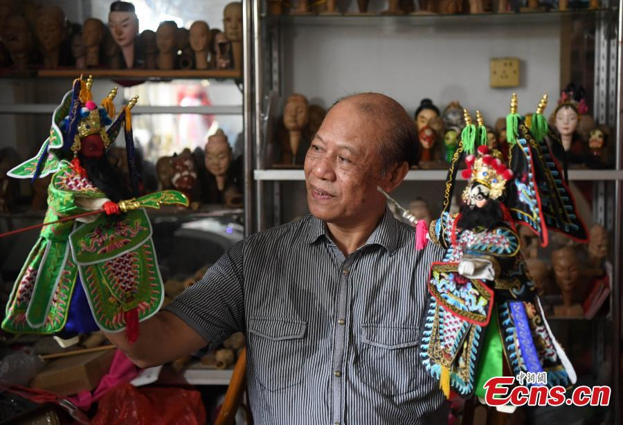 Folk artist Yang Yazhou shows his puppet head creations in his studio in Zhangzhou City, East China's Fujian Province, July 1, 2018. Zhangzhou has a history of puppetry going back more than two thousand years. Yang represents the fifth generation of his family to be involved with Fuchun-style glove puppets show, an intangible cultural heritage. He began learning to carve puppet heads when he was nine years old, taught by several masters. Yang said it takes tens of steps to finish carving a puppet-head in about three days. Yang's sister specializes in dressing the puppets, his brother in puppet performance. (Photo: China News Service/Zhang Bin)