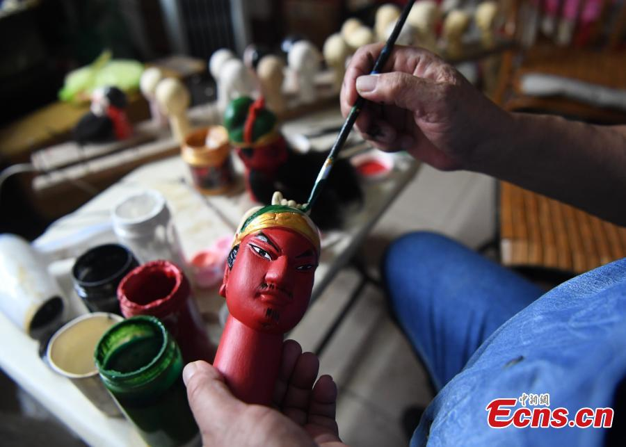 Folk artist Yang Yazhou paints the head of a puppet in his studio in Zhangzhou City, East China's Fujian Province, July 1, 2018. Zhangzhou has a history of puppetry going back more than two thousand years. Yang represents the fifth generation of his family to be involved with Fuchun-style glove puppets show, an intangible cultural heritage. He began learning to carve puppet heads when he was nine years old, taught by several masters. Yang said it takes tens of steps to finish carving a puppet-head in about three days. Yang's sister specializes in dressing the puppets, his brother in puppet performance. (Photo: China News Service/Zhang Bin)