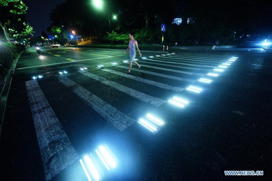A man walks on the lighted pedestrian crossing on Xixi Road in Hangzhou, capital of east China\'s Zhejiang Province, July 2, 2018. Lamps installed along the pedestrian crossing light up at night, giving directions to pedestrians and vehicles. (Xinhua/Long Wei)