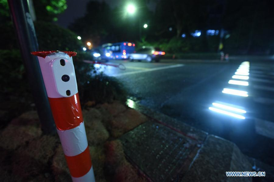 A lighted pedestrian crossing is seen on Xixi Road in Hangzhou, capital of east China\'s Zhejiang Province, July 2, 2018. Lamps installed along the pedestrian crossing light up at night, giving directions to pedestrians and vehicles. (Xinhua/Long Wei)