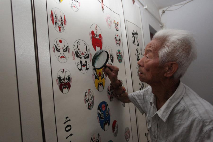 Zhang Fuli, 85, looks at his works of facial masks with a magnifying glass. (Photo//chinadaily.com.cn)
