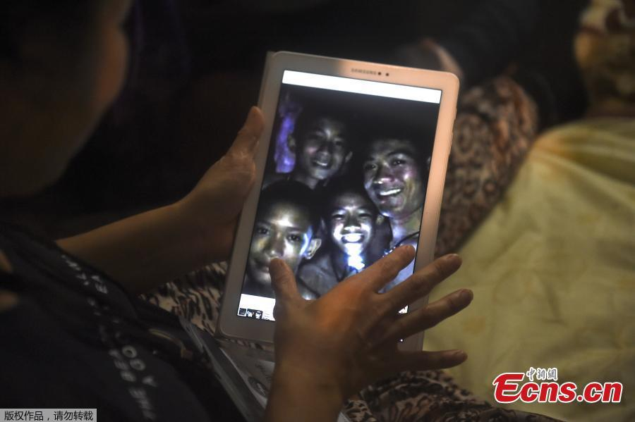 A family member shows a picture of four of the twelve missing boys near the Tham Luang cave at the Khun Nam Nang Non Forest Park in Mae Sai on July 2, 2018. Twelve boys and their football coach trapped in a flooded Thai cave for ten days were \