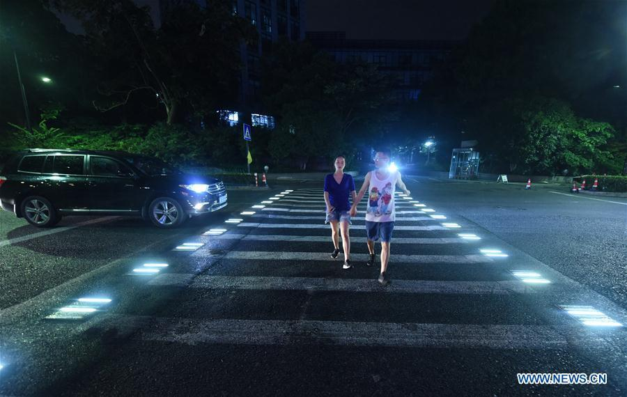 People walk on the lighted pedestrian crossing on Xixi Road in Hangzhou, capital of east China\'s Zhejiang Province, July 2, 2018. Lamps installed along the pedestrian crossing light up at night, giving directions to pedestrians and vehicles. (Xinhua/Long Wei)