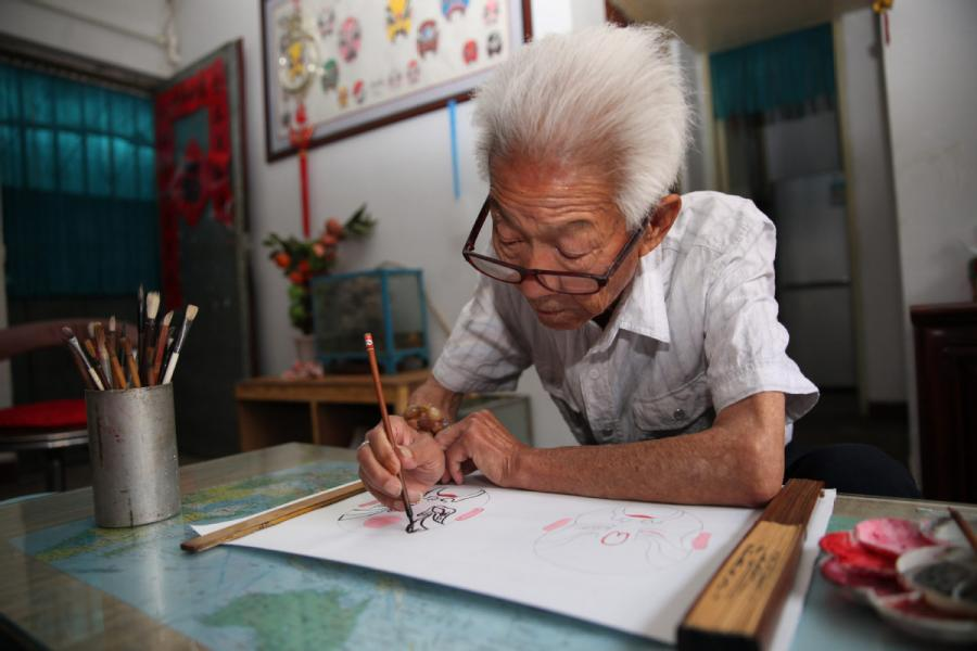 Zhang Fuli, 85, draws a facial mask of Peking Opera at home in Zhangjiakou, North China\'s Hebei Province.(Photo//chinadaily.com.cn)