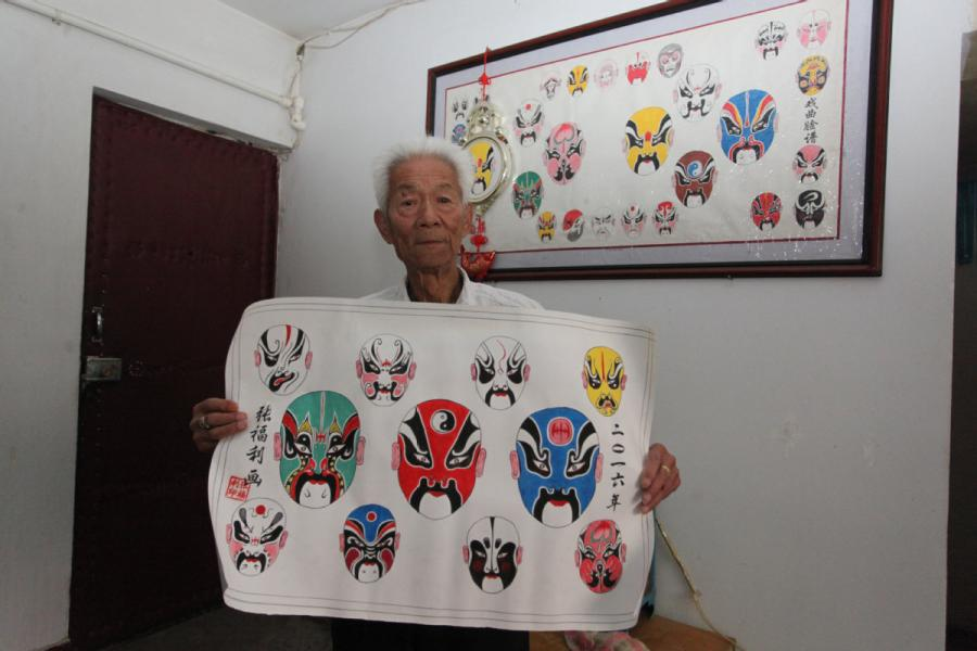 Zhang Fuli, 85, shows his painting works of Peking Opera facial masks.  (Photo//chinadaily.com.cn)