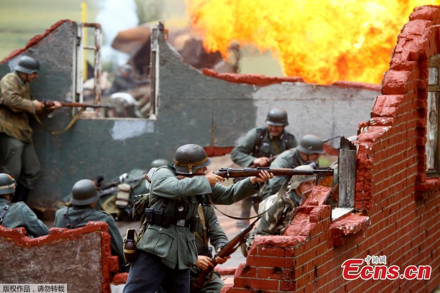Military enthusiasts take part in a re-enactment of a World War II battle on the eve of Independence Day at the \