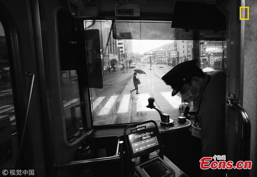 """Another Rainy Day in Nagasaki, Japan"" by Hiro Kurashina.  This is a view of the main street from a tram in Nagasaki on a rainy day. The tram is vintage and yet retrofitted with modern ticketing equipment. No conductor is on board any more - only the driver. (Photo/VCG)"