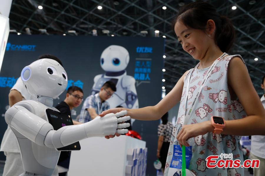 A girl interacts with a robot at the CIROS2018 (China International Robot Show) in Shanghai, July 4, 2018. More than 500 companies from 13 countries and regions showcased various robot products and services. (Photo: China News Service/Tang Yanjun)