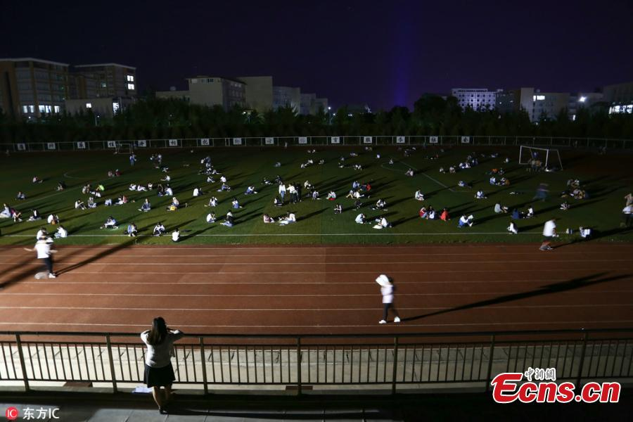 Students prepare for semester final exams on the football field of Qujing Medical College in Southwest China's Yunnan Province, July 4, 2018. Students used flashlights on their mobile phones, small chargeable table lamps, and the lights of the football field to help them revise outside on what was a hot summer night. (Photo/IC)