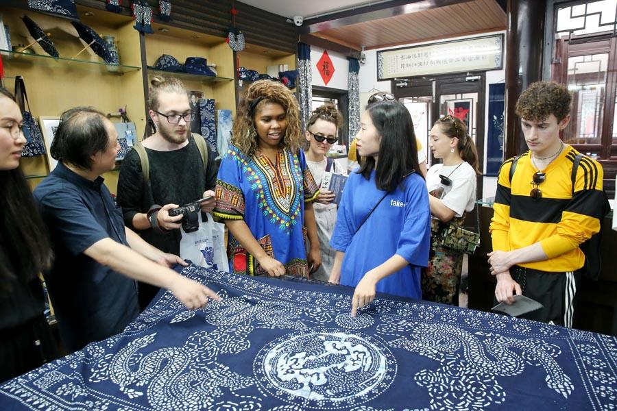 Chinese and British students from the China Academy of Art\'s creative fashion design camp listen to explanations of patterns on traditional Chinese blue calico in Nantong, East China\'s Jiangsu Province, on July 3, 2018.  (Photo/Asianewsphoto)