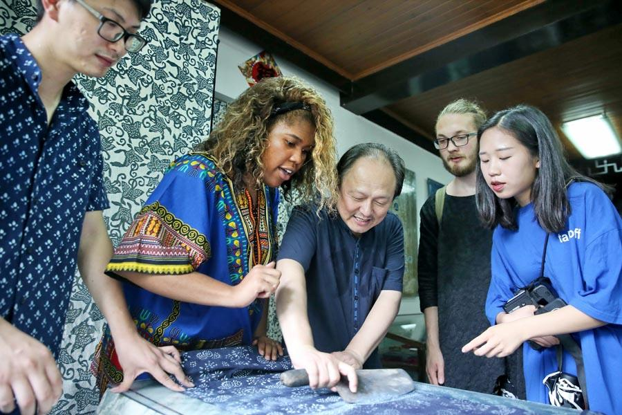 Chinese and British students from the China Academy of Art\'s creative fashion design camp observe traditional printing and dyeing of Chinese blue calico in Nantong, East China\'s Jiangsu Province, on July 3, 2018.  (Photo/Asianewsphoto)