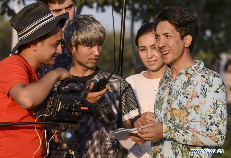 Daodao (1st R) and director Hezreteli Yasin (2nd L) who also acts in the comedy discuss scripts in Urumqi, northwest China\'s Xinjiang Uygur Autonomous Region, July 27, 2016. (Xinhua/Wang Fei)