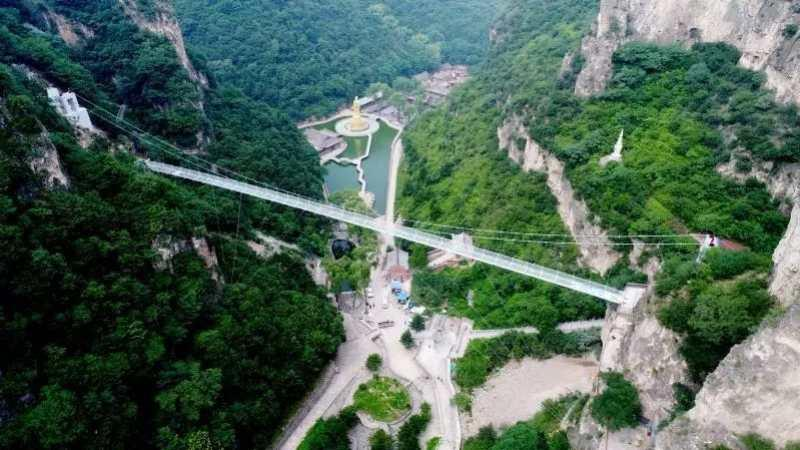 A 168-meter-long 5D glass suspension bridge opened to the public in Cangshan mountain scenic spot in Yuxian county in Shanxi on June 29, 2018. The bridge is 108 meters above the valley bottom. The glass, which is one meter thick, can bear a load of up to 6 tons. (Photo provided to chinadaily.com.cn)