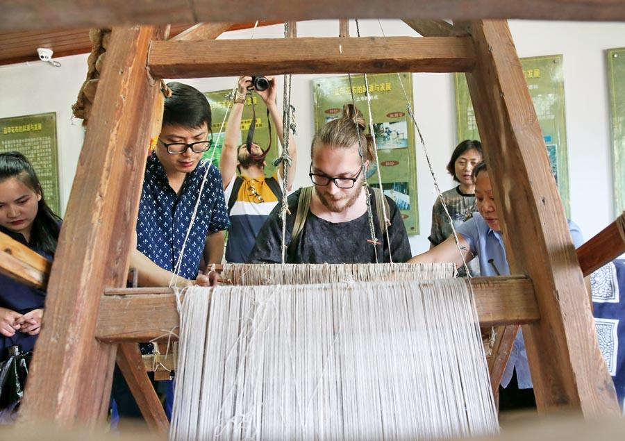 Chinese and British students from the China Academy of Art\'s creative fashion design camp experience traditional Chinese textile craft at the Blue Calico Museum in Nantong, East China\'s Jiangsu Province, on July 3, 2018. The process of making blue calico has been listed as a state-level intangible cultural heritage in China.  (Photo/Asianewsphoto)