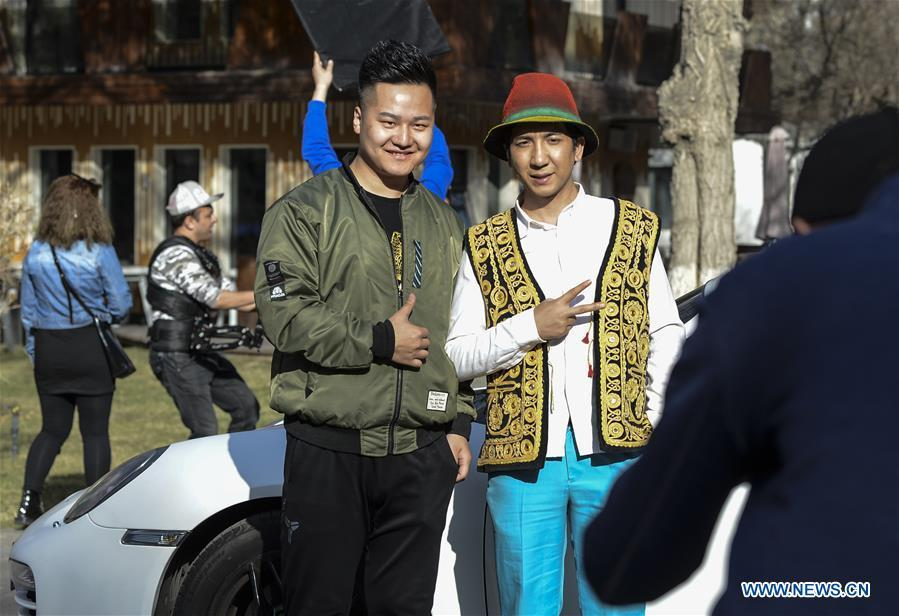 Daodao (R) poses for pictures with his fan when filming a music video in Urumqi, northwest China\'s Xinjiang Uygur Autonomous Region, March 30, 2018. (Xinhua/Wang Fei)