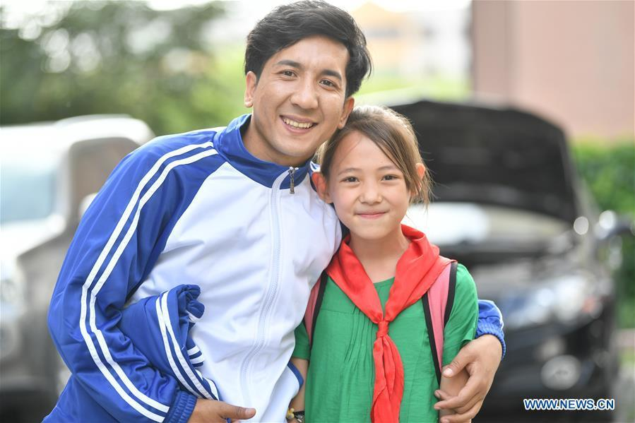 Daodao (L) poses for pictures with his fan in Urumqi, northwest China\'s Xinjiang Uygur Autonomous Region, June 7, 2018. (Xinhua/Wang Fei)