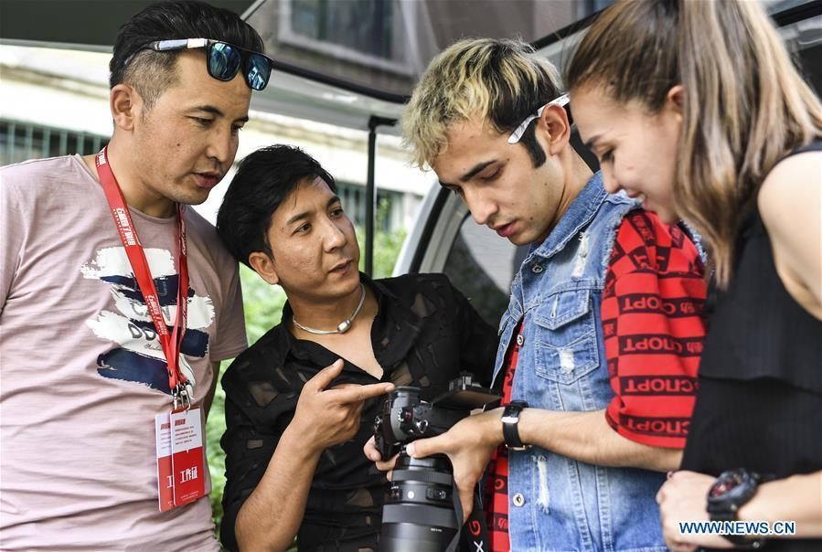 Daodao (2nd L) watches footage with other cast and crew members in Urumqi, northwest China\'s Xinjiang Uygur Autonomous Region, June 7, 2018. (Xinhua/Wang Fei)